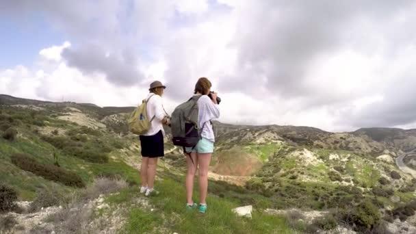 Két fiatal nők profi fotósok bevétel mozi-ból egy táj.