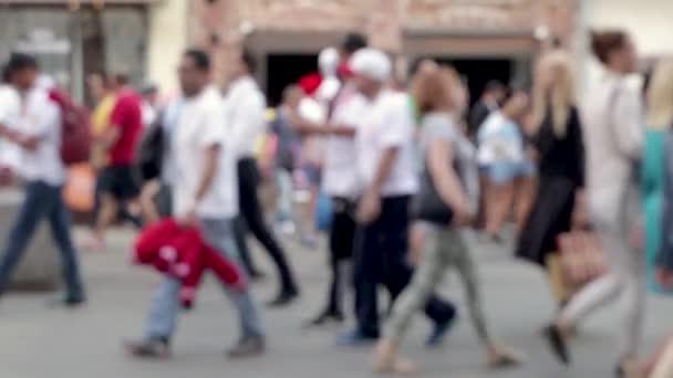 A crowd of people is walking down the street. Slow-motion defocused video.