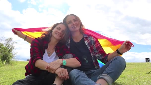 Two young women are sitting on a background of the rainbow flag. LGBT rights