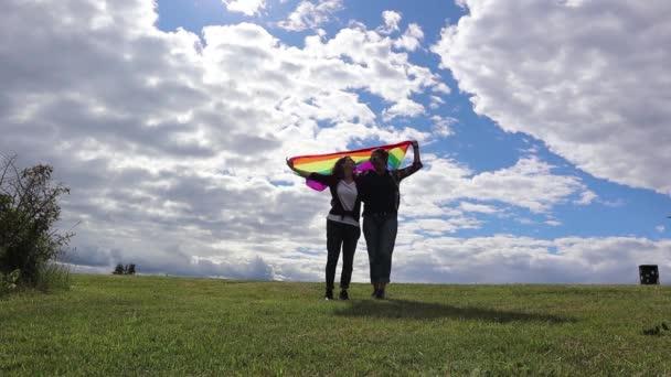 Dvě mladé ženy líbání na pozadí duhové vlajky