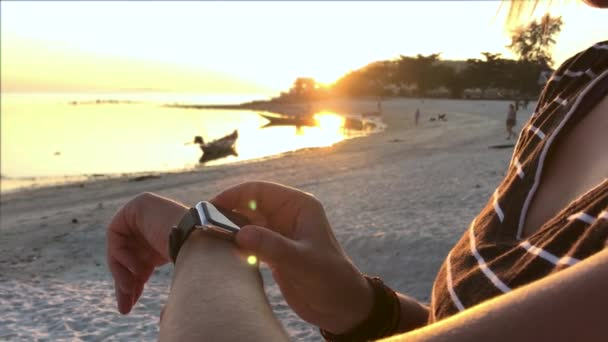 Smartwatch. Young woman using smart watch on beach. Closeup of female touching touch screen on watch entering watch app.