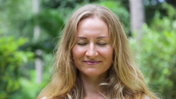 Gyönyörű fiatal nő, hosszú, szőke hajjal, nézi a kamerát, és a mosoly.