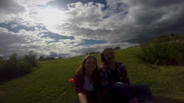 Dvě mladé ženy sedí na pozadí Duhová vlajka. Slunce svítí jasně, Lgbt práv, lesbická rodina