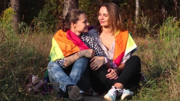 Dvě mladé ženy sedí na pozadí Duhová vlajka. Slunce svítí jasně, Lgbt práv, lesbická rodina.
