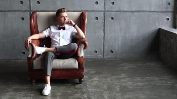Vážný mladý muž sedí v retro kožené křeslo