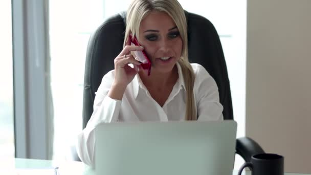 Young blond woman talking on the phone while sitting at the table in the office.