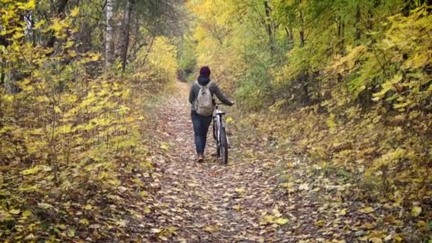 A young woman walking with a bicycle in the autumn forest.