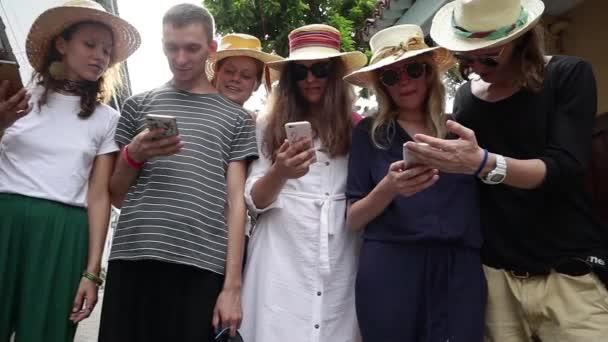 Egy csoport fiatal csípő emberek kalapok és napszemüveg áll az utcán azok okostelefonok. Vidám barátai, amelyek jó ideje együtt.