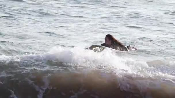 A young beautiful woman is swimming at the ocean on her surfboard.