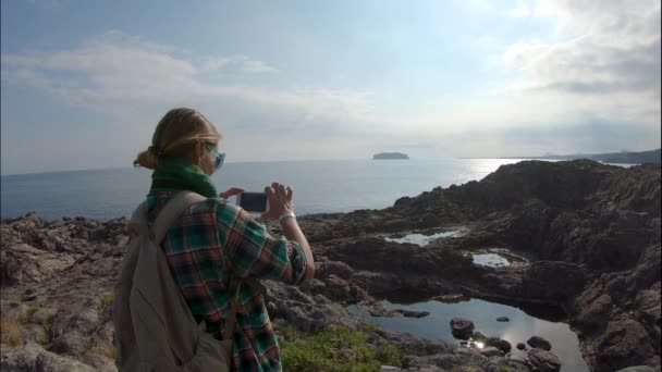 A young woman is taking pictures of a landscape with a smartphone.