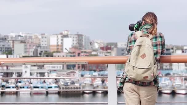 kaukasische freie Journalistin mit einer Kamera, die mit Booten eine Stadt und einen Hafen fotografiert. ein professioneller Fotograf, der mit einer Kamera unterwegs ist.