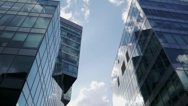 Budovy moderního kancelářského úřadu s odrazem skla. Mraky odrážející se po skle velké kancelářské budovy.