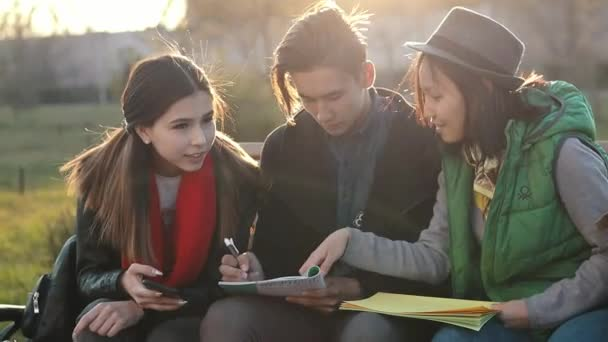 Three Asian teenagers doing homework at the park at the sunset time.
