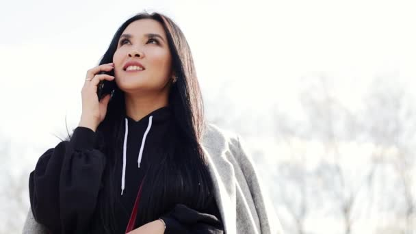 Beautiful young Asian girl with long black hair talking on a smartphone