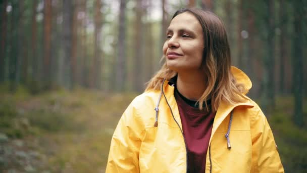 Portrait of a young woman in a bright yellow jacket standing at the rainy forest