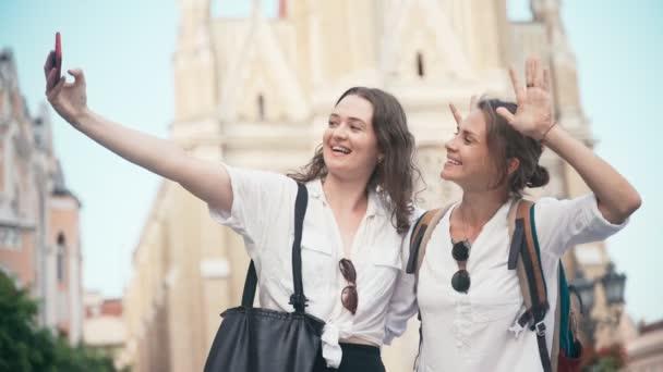 Dvě mladé veselé ženy se selfie s chytrým telefonem v centru města