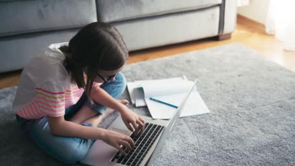 Vážné 8 let dívka v brýlích psaní na notebook zatímco sedí na koberci