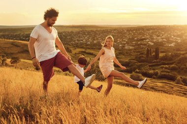 Happy family having fun walking in nature at sunset
