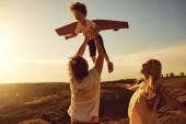 Fotografie Familie spielen in der Natur bei Sonnenuntergang