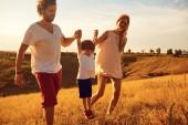 Fotografie Glückliche Familie Spaß spielen bei Sonnenuntergang.