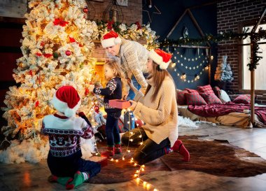 A happy family decorates a Christmas tree at home.