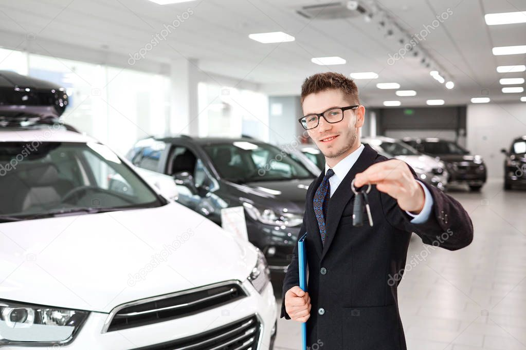 Il venditore di auto con le chiavi in mano nello showroom auto .