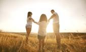 Fotografie Glückliche Familie auf die Natur im Sommer bei Sonnenuntergang.