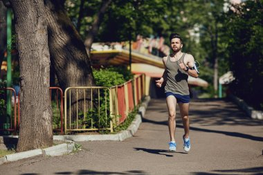 A male runner runs along the road to the park.