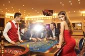 Žena s oblečena u stolu rulette v kasinu.