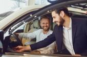 Prodejce aut ukazuje nové auto pro muže