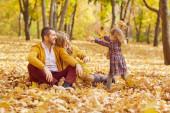 Rodina hrající si s dítětem v parku na podzim.