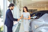 Girl buyer shakes hands dealer car