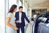Mladá žena kupuje nové auto v autosalonu