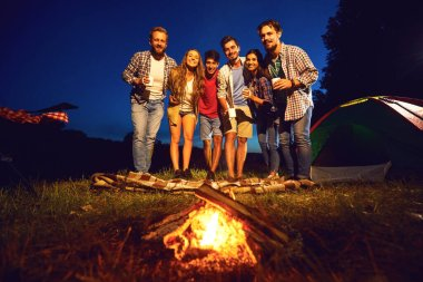 A group of people standing by the bonfire next to the tent at night in the summer in autumn.