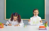 Fotografie Holčičky kreslí ve škole, kopírují prostorový text. Roztomilé děti na lekci ve třídě