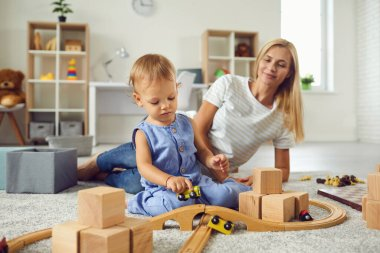 Young babysitter and little child playing with wooden blocks in cozy nursery room