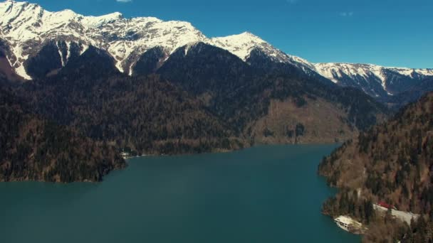A view of the high mountains with snow tops, at the foot of the lake and buildings