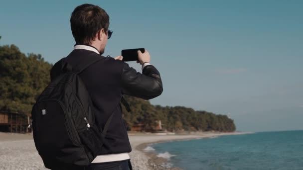 Mann macht eine Reihe von Fotos auf dem Hintergrund des Meeres, kann er ein tourist