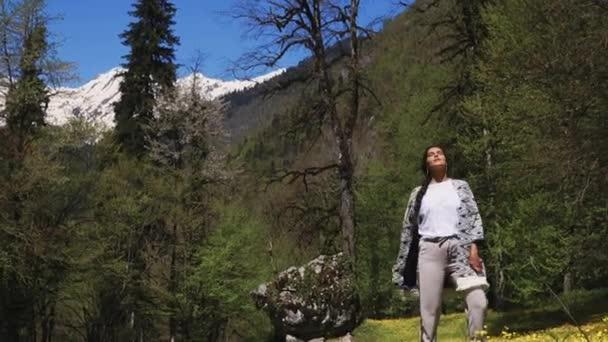 Žena chodí sám na slunné louce s květinami nedaleko lesa v denní
