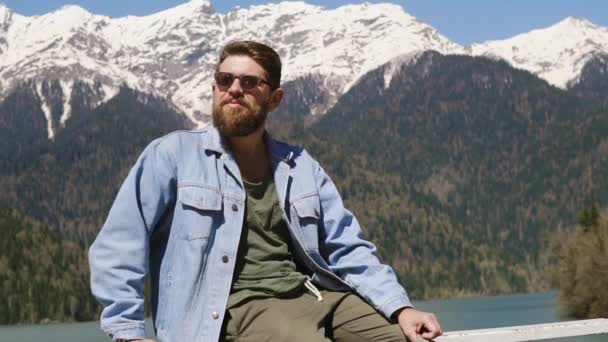 Cheerful bearded man is sitting and resting in background of amazing mountains