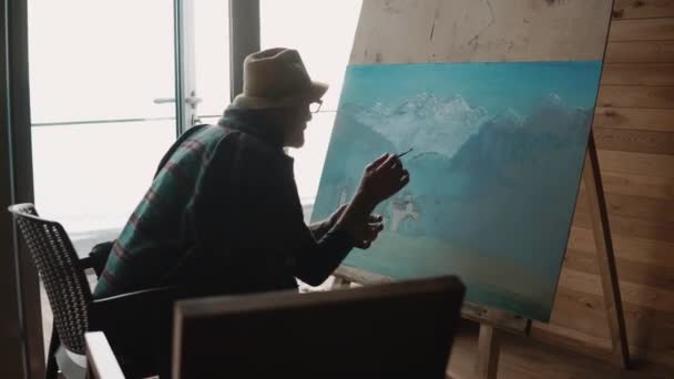 Old and exprienced artist is drawing a beautiful painting of nature. Old man drawing landscape in a workshop.