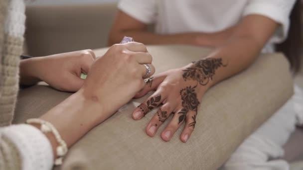 Detailní záběr záběr použití henna s kužel na Zenske ruky. Umění tradiční mehndi je krytý. Henna tetování na rukou