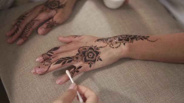 close up shot of a womans hands, who rests with a friend while drawing mehendi