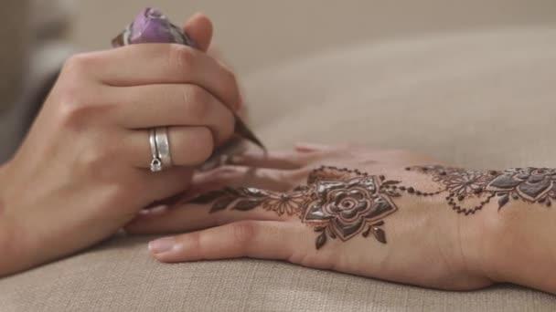 Közelről lövés womans kéz a a henna kúp, ennek a gyönyörű mehndi művészet a bőr. Rajz-a ujjak. Szép virágok.