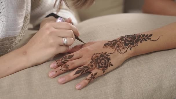 Woman Is Drawing Mehndi Designs On Hands Of Her Friend Girl Close