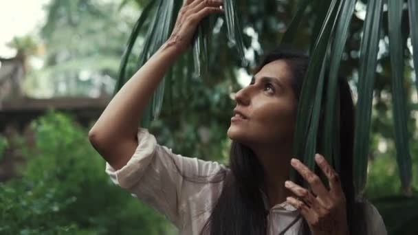 portrét ženy, která předá její ruku nad list z palmu v parku