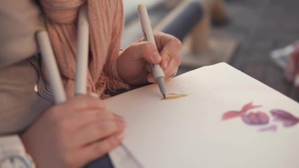 Nő a virágmotívumok rajz egy vázlatfüzet, ül egy kerti, közeli