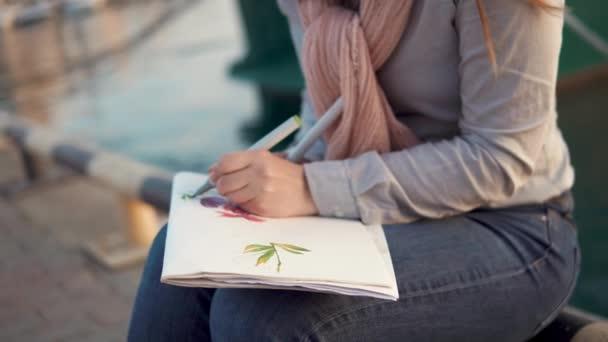 Ženské ruce kreslení jsou květiny v skicáře, detail mimo poblíž moře