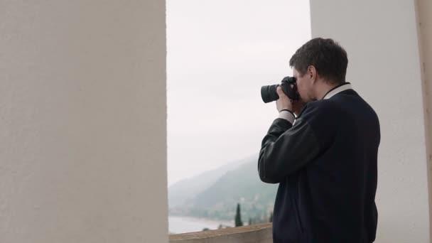 männlicher Fotograf beobachtet im Objektiv der Kamera eine Landschaft