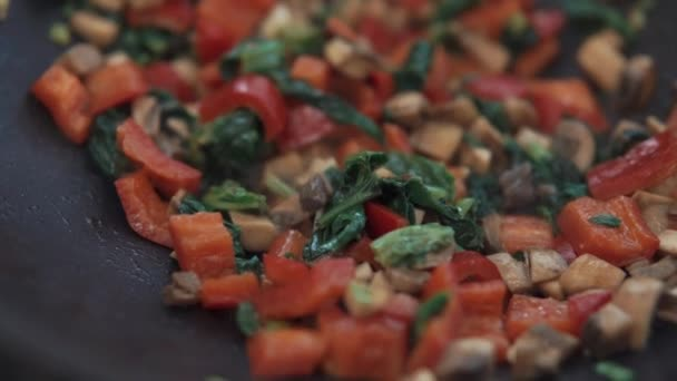 Close-up of cut red vegetables with herbs are frying in a pan on stove